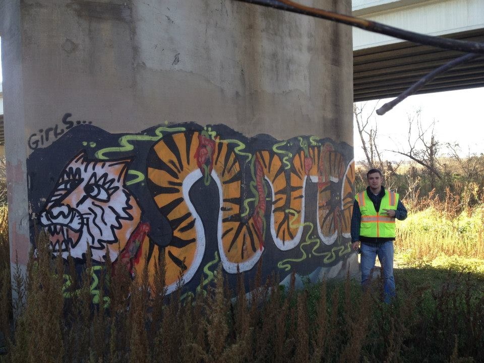 An Infrasense engineer posing with this wild tiger graffiti we spotted under a bridge in Minnesota.